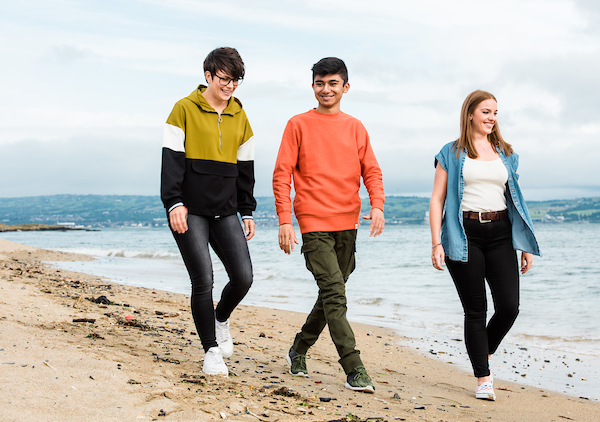 two adult females with teenage boy walking on beach