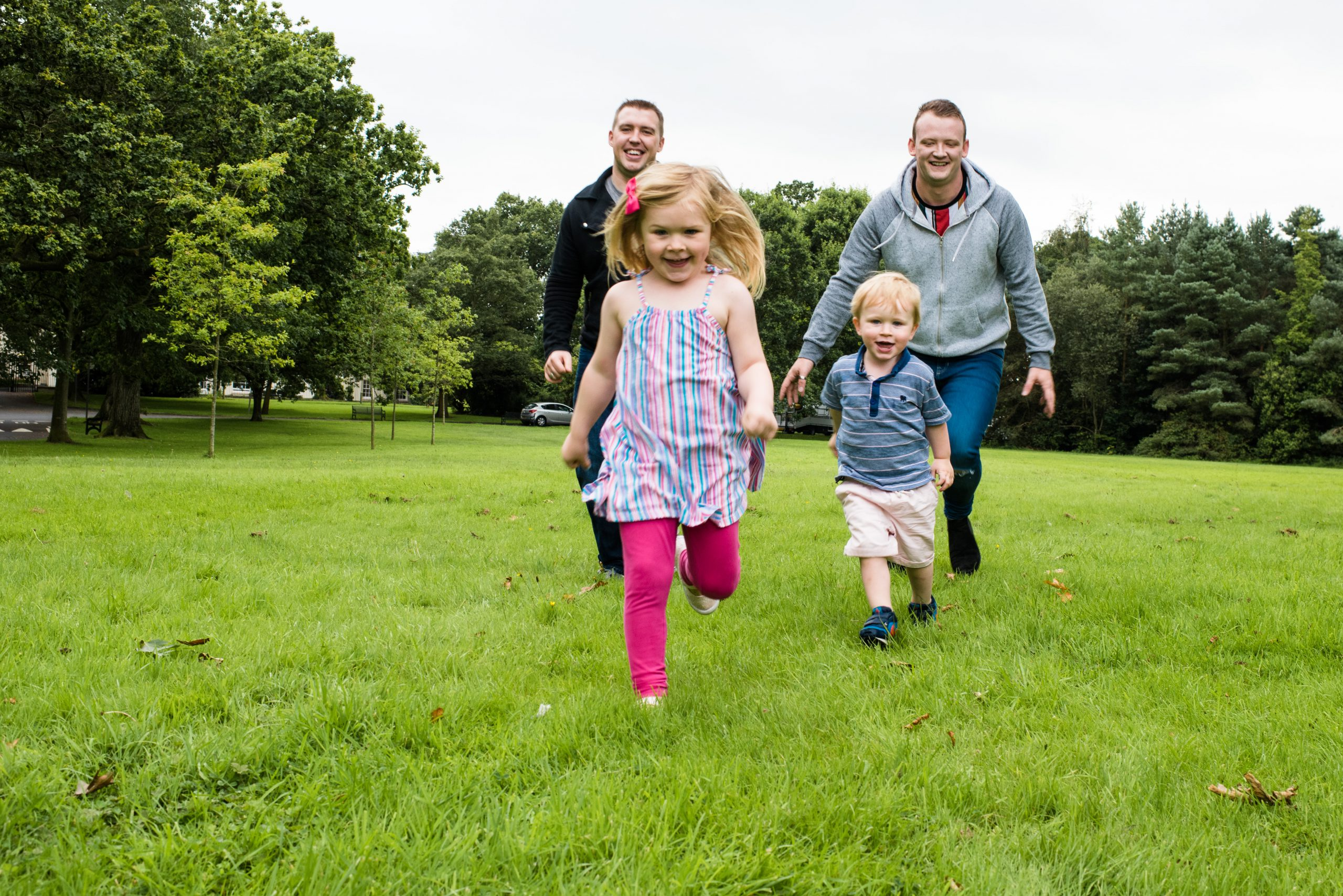 two adult male playing with two children in a park